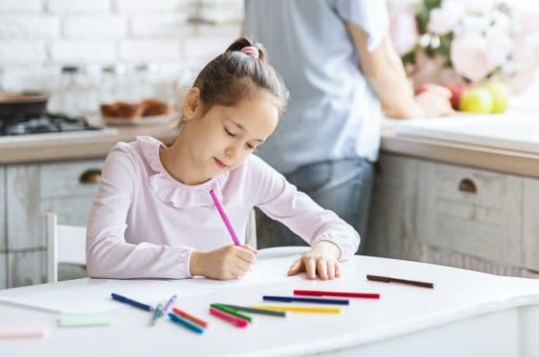 Pretty little girl busy with drawing at kitchen table