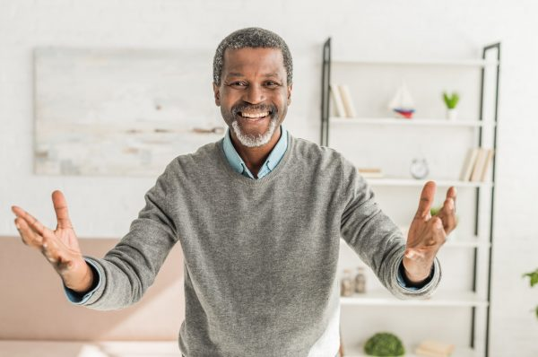 happy african american man looking at camera and showing welcome gesture